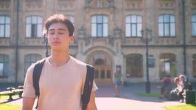 Frisches Trieb des netten asiatischen Jungen, der in Richtung zur Kamera geht und Vorwärts schaut, während es sonnige perfekte He stock video