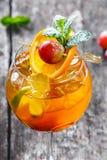 Frisches tropisches Cocktail mit Minze, Orange und Kalk im hohen Glas auf hölzernem Hintergrund Lizenzfreie Stockfotografie