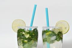 Frisches und kaltes Mojito-Cocktail auf einem weißen Hintergrund Mojito zwei Lizenzfreie Stockfotos