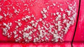 Frisches weißes Eis nach Regen auf einem roten Auto im Winter Seite eines gefrorenen Autos an einem kalten Wintermorgen Stockfotos