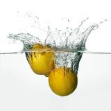 Frisches Zitronen-Spritzen im Wasser lokalisiert auf weißem Hintergrund Stockfoto
