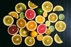 Frisches Zitrusfrucht stihli Zitronen, Kalke, Pampelmuse und Orange auf einem schwarzen Hintergrund Lizenzfreie Stockbilder