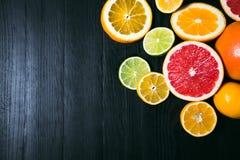Frisches Zitrusfrucht stihli Zitronen, Kalke, Pampelmuse und Orange auf einem schwarzen Hintergrund Stockfotografie