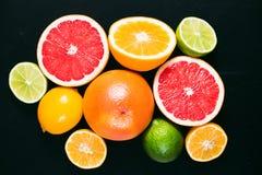 Frisches Zitrusfrucht stihli Zitronen, Kalke, Pampelmuse und Orange auf einem schwarzen Hintergrund Stockfoto