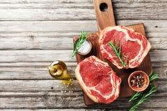 Frischfleisch auf Draufsicht des hölzernen Schneidebretts Rohes Rindfleischsteak und -gewürze für das Kochen stockbild