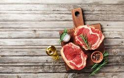 Frischfleisch auf Draufsicht des hölzernen Schneidebretts Rohes Rindfleischsteak und -gewürze für das Kochen lizenzfreies stockfoto