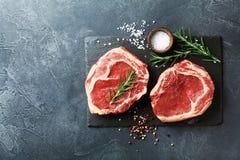 Frischfleisch auf Draufsicht des Schieferschwarzbrettes Rohes Rindfleischsteak und -gewürze für das Kochen lizenzfreies stockfoto