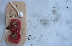 Frischfleisch auf einem hölzernen Brett mit den Gewürzen und Salz bereit zum Kochen lizenzfreies stockfoto