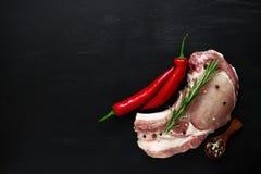 Frischfleisch mit einer Rosmarinniederlassung und einem glühenden gedämpften Pfeffer Ansichtspitzenkopienraum Lizenzfreie Stockbilder