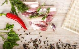 Frischfleisch: rohes Schweinefleisch mit Pfeffer des roten Paprikas, Dill, Knoblauch und Rosmarin Stockfoto