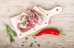 Frischfleisch: rohes Schweinefleisch mit Pfeffer des roten Paprikas, Dill und Rosmarin auf hölzernem Brett Lizenzfreies Stockfoto