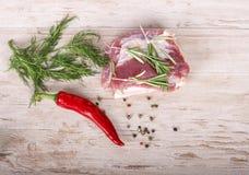 Frischfleisch: rohes Schweinefleisch mit Pfeffer des roten Paprikas, Dill und Rosmarin auf hölzernem Brett Stockfoto