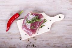 Frischfleisch: rohes Schweinefleisch mit Pfeffer des roten Paprikas, Dill und Rosmarin auf hölzernem Brett Stockfotos