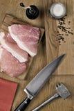 Frischfleischsteaks auf einem Schneidebrett mit einem Messer und einem Hammer Stockbild