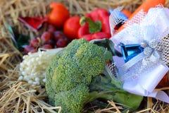 Frischgemüse Brokkoli und Trauben auf Stroh Stockbilder