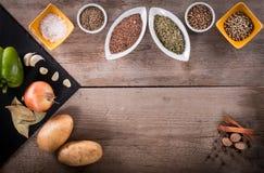 Frischgemüse, Gewürze und Kräuter in den Schüsseln Natürliche und Biobestandteile für das Kochen auf hölzernem Hintergrund lizenzfreie stockbilder