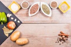 Frischgemüse, Gewürze und Kräuter in den Schüsseln Natürliche und Biobestandteile für das Kochen auf hölzernem Hintergrund stockfotografie