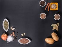Frischgemüse, Gewürze und Kräuter zerstreuten auf dunklen Hintergrund Natürliche und Biobestandteile für das Kochen des Kopienrau stockbilder