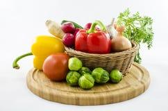 Frischgemüse im Weidenkorb auf hölzernem Brett Lizenzfreies Stockfoto