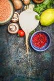 Frischgemüse und Bestandteile mit roter Linse für das gesunde Kochen auf rustikalem Hintergrund, Draufsicht, vertikale Grenze Stockbild