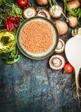 Frischgemüse und Bestandteile mit roter Linse für das gesunde Kochen auf rustikalem Hintergrund, Draufsicht, vertikale Grenze Lizenzfreies Stockfoto