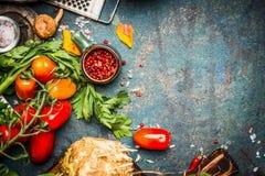Frischgemüse und Gewürzbestandteile für den geschmackvollen Vegetarier, der auf dunklem rustikalem Hintergrund kocht Lizenzfreie Stockbilder
