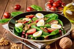 Frischgemüsesalat mit Spinat, Kirschtomaten, Wachteleiern, Granatapfelsamen und Walnüssen im Schwarzblech auf Holztisch Stockbild