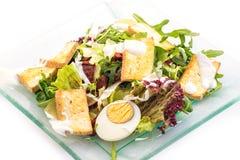 Frischgemüsesalat vom Arugula, vom Käse und von den Eiern auf der Glasplatte lokalisiert auf weißem Hintergrund, Produktfotografi Stockfotos