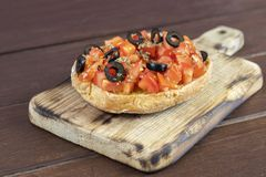 Freselle,or friselle dried bread, italian food. Friselle or Freselle Italian appetizer on wooden board with tomatoes, garlic,black olives, oregano, salt, and royalty free stock photography