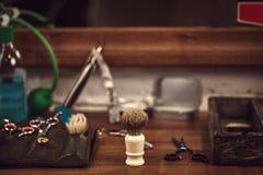 Frisersalonghjälpmedel på den träbruna tabellen Tillbehör för att raka och frisyrer på tabellen fotografering för bildbyråer