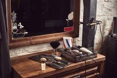 Frisersalonghjälpmedel på den träbruna tabellen Tillbehör för att raka och frisyrer på tabellen arkivfoton