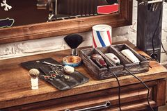 Frisersalonghjälpmedel på den träbruna tabellen Tillbehör för att raka och frisyrer på tabellen royaltyfri fotografi