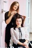 Friseur bei der Arbeit - der Friseur tut das Haar eines schönen jungen Brunette den Kunden im Schönheitssalon an lizenzfreies stockfoto