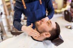 Friseur, der Aftershavelotion am männlichen Hals anwendet lizenzfreie stockfotografie