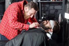 Friseur, der Barthaarschnitt unter Verwendung des Rasierapparates macht Stockfoto