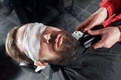 Friseur, der Barthaarschnitt unter Verwendung des Rasierapparates macht Stockbild