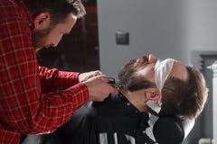 Friseur, der Barthaarschnitt unter Verwendung des Rasierapparates macht Lizenzfreie Stockfotografie