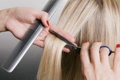 Friseur, der blondes Haar schneidet Stockfotografie