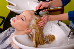Friseur, der blondes Haar wäscht Lizenzfreies Stockfoto