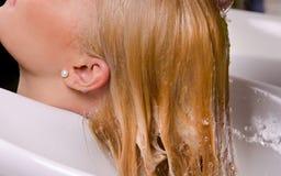 Friseur, der blondes Haar wäscht Stockbild
