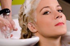 Friseur, der blondes Haar wäscht Lizenzfreie Stockfotos