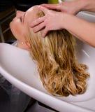 Friseur, der blondes Haar wäscht Stockfotos