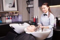 Friseur, der das blonde Haar einer Frau wäscht lizenzfreies stockbild