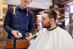 Friseur, der das Haar anredet Wachs zum männlichen Kunden zeigt stockfoto