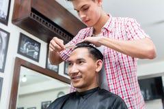 Friseur, der das Kunde ` s Haar kämmt lizenzfreies stockfoto