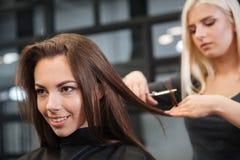 Friseur, der dem weiblichen Kunden einen neuen Haarschnitt am Wohnzimmer gibt Lizenzfreie Stockfotos