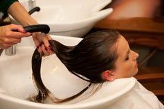 Friseur, der einem Kunden im Salon Haarbehandlung macht Lizenzfreie Stockfotos