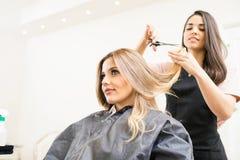 Friseur, der einige Haartipps schneidet Stockfoto