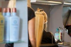 Friseur, der Extensionen an einem Klienten anwendet lizenzfreie stockbilder