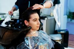 Friseur, der junges Kundinhaar im Salon wäscht lizenzfreie stockbilder